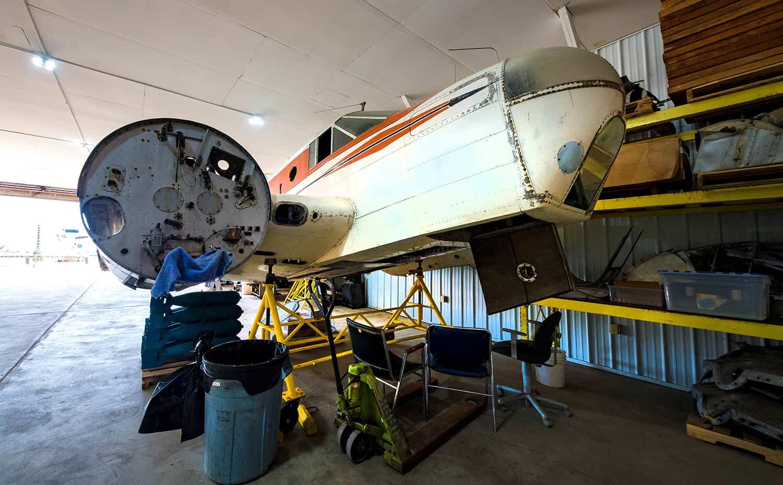 Wings Restorations Hangar. Hangar door open with the Vultee BT-15 sitting outside in the sun.